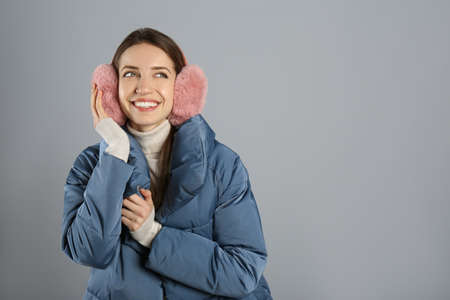 Happy woman wearing warm earmuffs on gray background, space for text