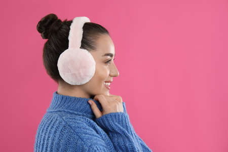 Beautiful young woman wearing earmuffs on pink background. Space for text