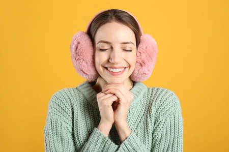 Happy woman wearing warm earmuffs on yellow background
