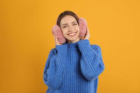 Happy woman wearing warm earmuffs on yellow background Reklamní fotografie