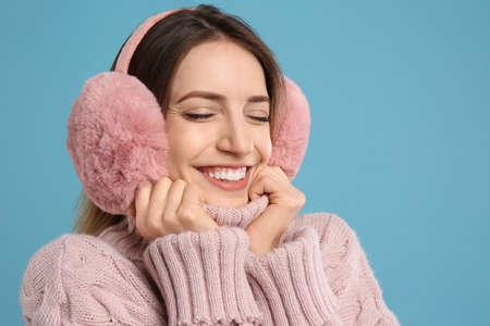 Happy woman wearing warm earmuffs on light blue background Reklamní fotografie