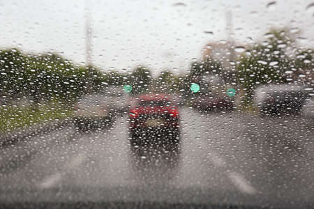Blurred view of road through wet car window. Rainy weather 版權商用圖片