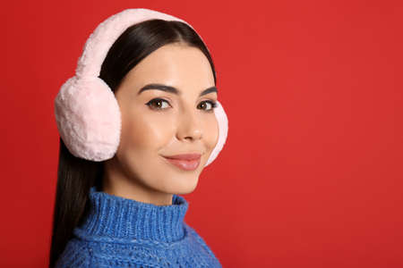 Beautiful young woman wearing earmuffs on red background. Space for text Reklamní fotografie