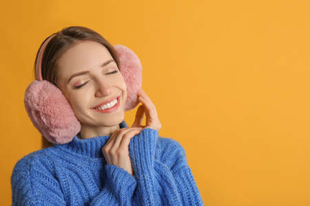 Happy woman wearing warm earmuffs on yellow background, space for text Reklamní fotografie