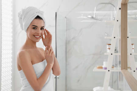 Happy young woman with towel on head in bathroom, space for text. Washing hair