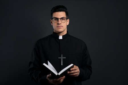 Priest in cassock with Bible on black background