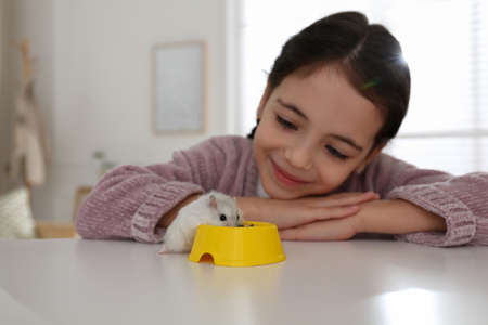Little girl with cute hamster at table indoors