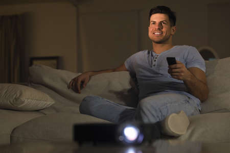 Man watching movie on sofa at night, space for text