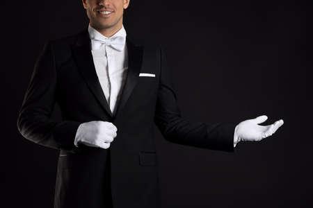 Butler in elegant uniform on black background, closeup Фото со стока