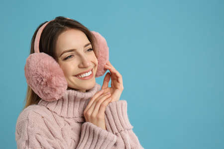 Happy woman wearing warm earmuffs on light blue background, space for text Фото со стока