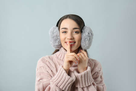 Beautiful young woman wearing earmuffs on light gray background