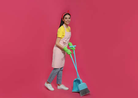 Young housewife with broom and scoop on pink background