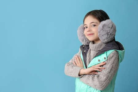 Cute little girl wearing stylish earmuffs on light blue background. Space for text Reklamní fotografie