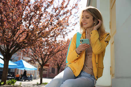 Young woman listening to audiobook on city street. Space for text
