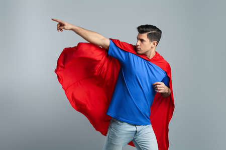 Man wearing superhero cape on gray background Фото со стока