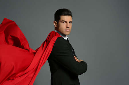 Businessman wearing superhero cape on gray background Фото со стока