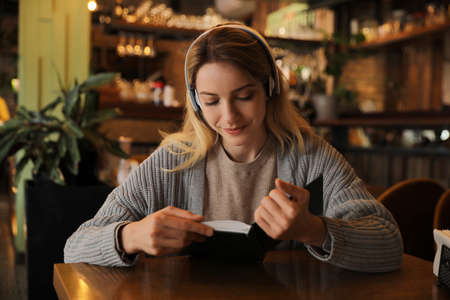 Woman listening to audiobook at table in cafe Фото со стока
