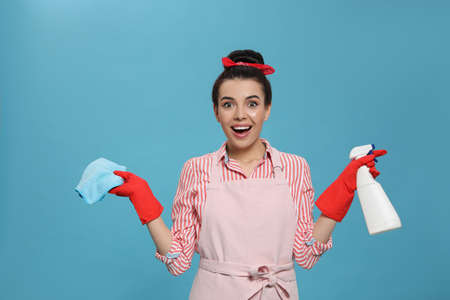 Emotional housewife with detergent and rug on light blue background