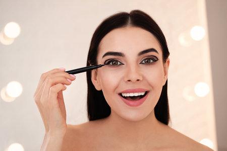 Beautiful young woman applying black eyeliner indoors