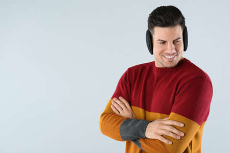 Man wearing stylish earmuffs on light background. Space for text