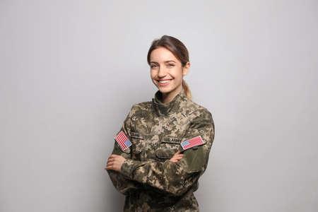 Portrait of happy female cadet on light gray background Фото со стока