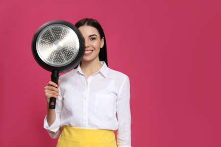 Young housewife with frying pan on pink background, space for text
