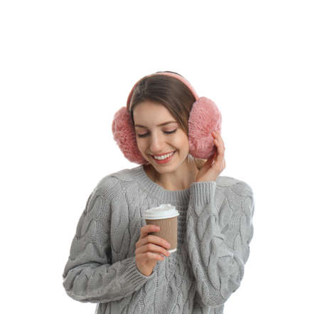 Happy woman with cup of drink wearing warm earmuffs on white background Reklamní fotografie