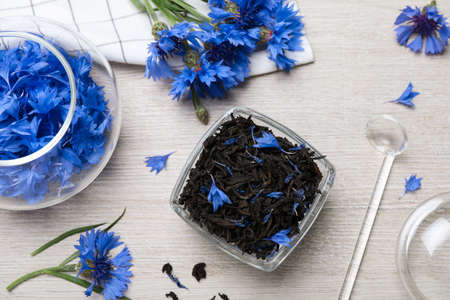 Composition with dry tea leaves and cornflowers on white wooden table, flat lay