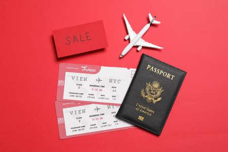 Flight tickets, passport, plane model and SALE card on red background, flat lay Reklamní fotografie