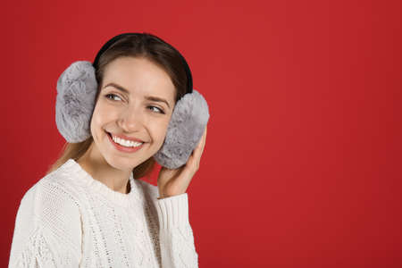 Happy woman wearing warm earmuffs on red background, space for text