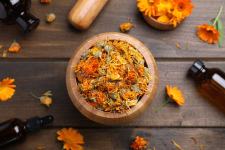 Dry calendula flowers and bottles of essential oil on wooden table, flat lay