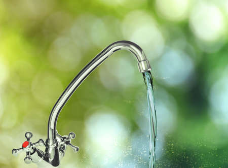 Water flowing from tap outdoors on sunny day, bokeh effect