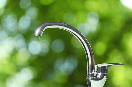 Water drop flowing from tap outdoors on sunny day, bokeh effect Stockfoto
