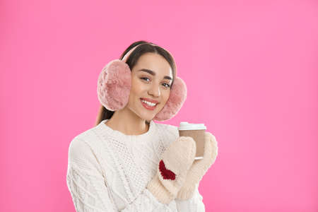 Beautiful young woman in earmuffs with cup of drink on pink background