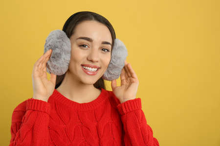 Beautiful young woman wearing earmuffs on yellow background. Space for text Reklamní fotografie