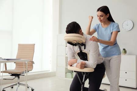 Man receiving massage in modern chair indoors
