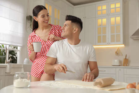 Happy couple wearing pyjamas and cooking together in kitchen Фото со стока