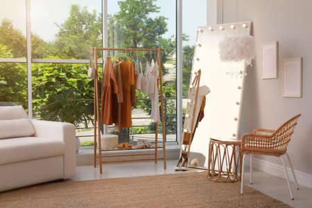 Dressing room interior with clothing rack and comfortable furniture Фото со стока