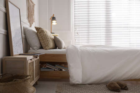Comfortable bed with clean white linens indoors