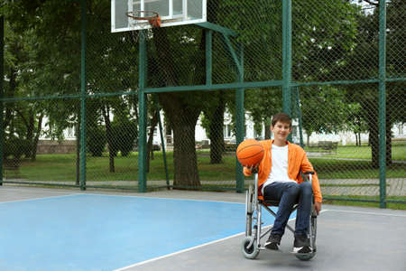 Disabled teenage boy in wheelchair with basketball ball at outdoor court