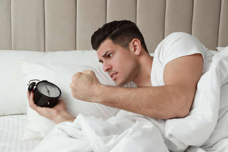 Emotional man with alarm clock in bed. Being late because of oversleeping Standard-Bild