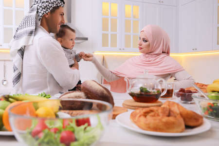 Happy Muslim family with little son at served table in kitchen Фото со стока