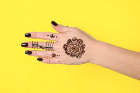 Woman with henna tattoo on hand against yellow background, closeup. Traditional mehndi ornament