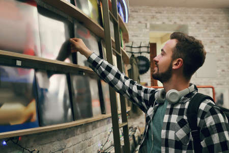Young man choosing vinyl records in store