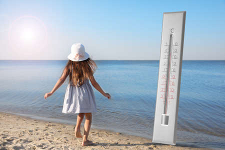 Weather thermometer and little child running on sandy beach. Heat stroke warning