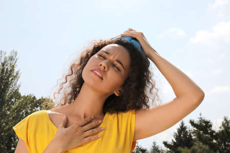 African-American woman with cold pack suffering from heat stroke outdoors