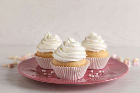 Delicious cupcakes with cream on white wooden table