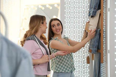 Women choosing jeans to buy in showroom Фото со стока