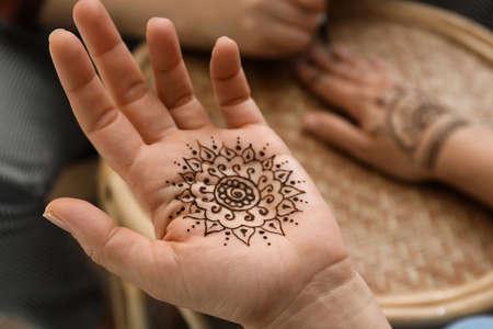 Master making henna tattoo, focus on hand. Traditional mehndi