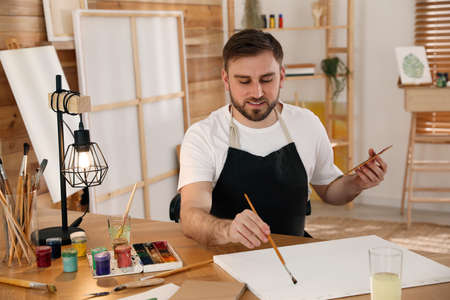 Young man painting with brush in artist studio
